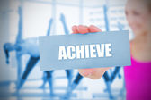 Fit blonde holding card saying achieve — Stock Photo