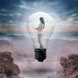 Woman holding laptop in light bulb — Stock Photo #44894357
