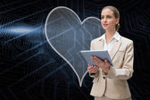 Heart and businesswoman using tablet — Stock Photo