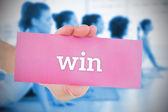Woman holding pink card saying win — Stockfoto