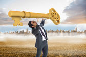Stressed businessman carrying large key — Stock Photo