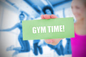 Fit blonde holding card saying gym time — Stock Photo