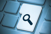 Composite image of magnifying glass on enter key — Stock Photo
