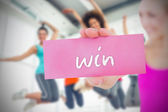 Woman holding pink card saying win — Stock Photo