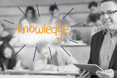 Knowledge against lecturer standing in front of his class in lecture hall — Stock Photo