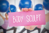 Woman holding pink card saying body sculpt — Stock Photo