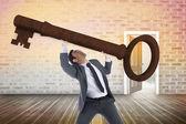 Unsmiling businessman carrying large key — Stock Photo