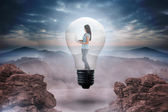 Woman holding laptop in light bulb — Stock Photo