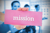 Woman holding pink card saying mission — Stock Photo