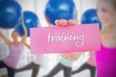 Woman holding pink card saying  training — Stock Photo