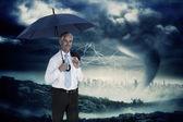 Businessman holding umbrella — Stock Photo