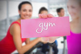 Woman holding pink card saying gym — Stock Photo