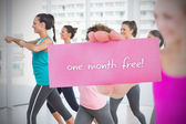 Woman holding pink card saying one month free — Stockfoto