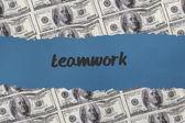 Teamwork against digitally generated sheet of dollar bills — Stockfoto