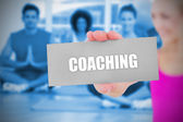 Fit blonde holding card saying coaching — Stock Photo