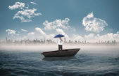 Businessman holding umbrella in a sailboat — Stock Photo