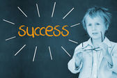 Success against schoolboy and blackboard — Stock Photo