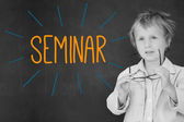 Seminar against schoolboy and blackboard — Stock Photo
