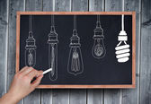 Hand drawing light bulbs with chalk — Stock Photo
