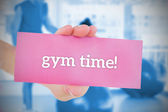 Woman holding pink card saying gym time! — Stock Photo
