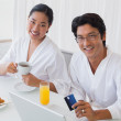 Couple in bathrobes shopping online in the morning — Stock Photo #45104633