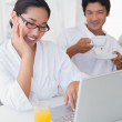 Couple in bathrobes spending the morning together using laptop — Stock Photo #45108153
