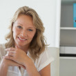 Casual businesswoman smiling at camera at her desk — Stock Photo