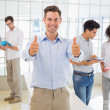 Casual boss giving thumbs up at camera in front of business team — Stock Photo #45109893