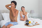Smiling woman watching her boyfriend yawn and stretch — Stock Photo