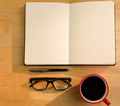 Overhead of open notebook with pen glasses and coffee — Stock Photo
