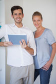 Casual business team smiling at camera man holding tablet — Stock Photo