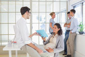 Pregnant businesswoman talking with colleague — Stock Photo