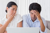 Worried couple using laptop together — Stock Photo