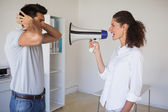 Casual businesswoman shouting at colleague through megaphone — Stock Photo