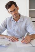 Lässig geschäftsmann notizen an seinem schreibtisch — Stockfoto
