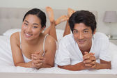 Happy couple lying on bed together — Stock Photo