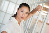 Casual frowning businesswoman leaning on window — Stock Photo