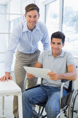 Businessman in wheelchair with colleague — Stock Photo