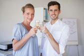 Casual business team smiling at camera toasting with champagne — Stock Photo