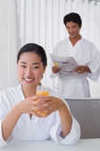 Woman in bathrobe having orange juice with boyfriend in background — Stock Photo