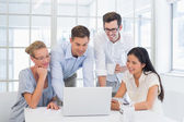 Business team looking at laptop together — Stock Photo