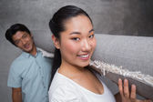 Happy couple holding a rolled up rug — Stock Photo