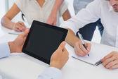 Casual affärsman med sin tablett under möte — Stockfoto
