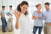Casual businesswoman giving ok sign to camera — Stock Photo