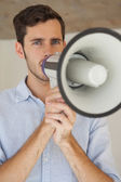 Casual businessman talking through megaphone — Stock Photo