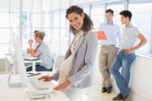 Pregnant businesswoman with team behind her — Stock Photo