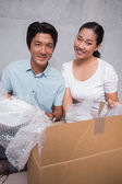 Happy couple sitting on floor unpacking boxes — Stock Photo