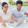 Smiling couple having breakfast together using laptop — Stock Photo #45110915