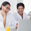 Couple in bathrobes spending the morning together using laptop — Stock Photo #45110919
