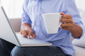 Man sitting on couch using laptop having coffee — Stock Photo